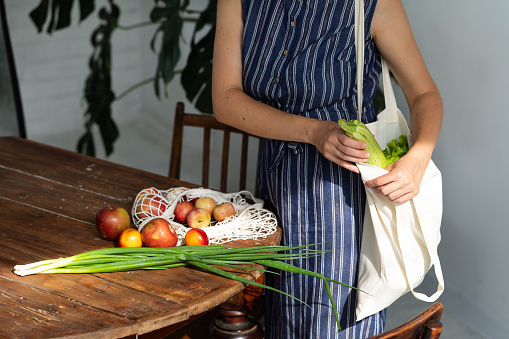 Young woman with shopping cotton Eco bag with fruits and vegetables in her hands near wooden table at home. Lifestyle, zero waste concept