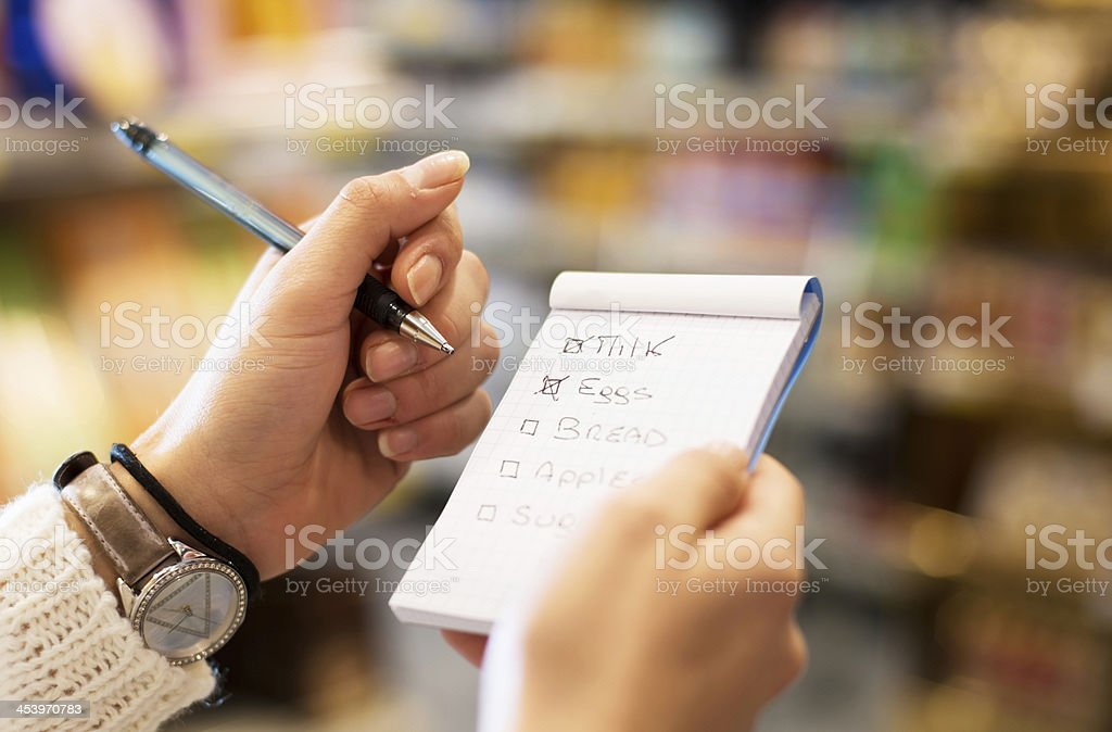 young woman with shopping list at supermarket stock photo