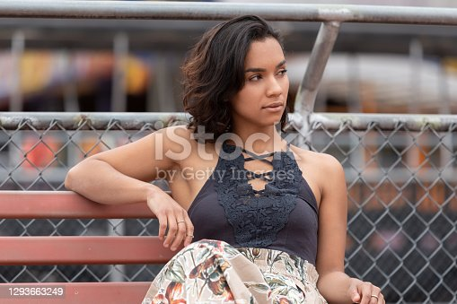 Young brunette Latin woman with short hair and curls distracted and looking to the side, sitting on a bench in a park, has a casual outfit