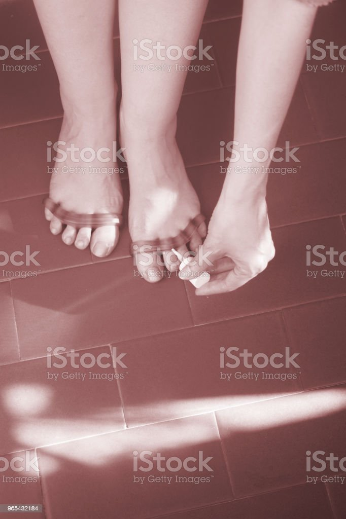 Young woman with silicone toe separator to separate toes to pedicure and paint or file toenails. zbiór zdjęć royalty-free