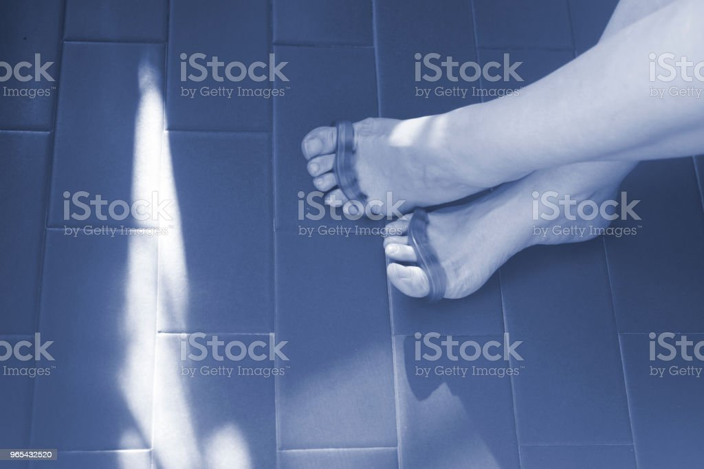 Young woman with silicone toe separator to separate toes to pedicure and paint or file toenails. royalty-free stock photo