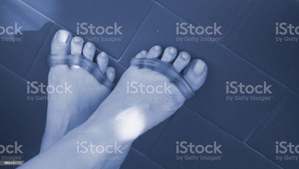 年輕婦女與矽膠腳趾分離器分開腳趾到修腳和油漆或檔腳趾甲。 - 免版稅人圖庫照片