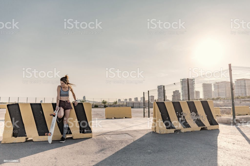 Young woman with skateboard at sunset in the city stock photo