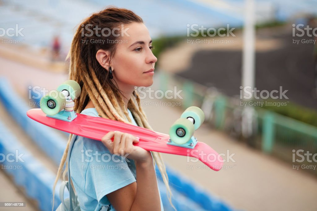 Young woman with skateboard in the stadium stock photo