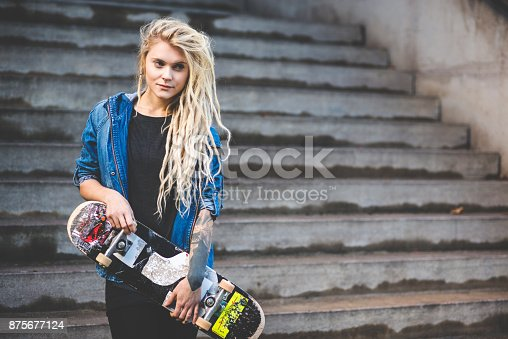 istock Young woman with skateboard on staircase 875677124