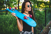 Beautiful young caucasian woman standing with skateboard outdoors