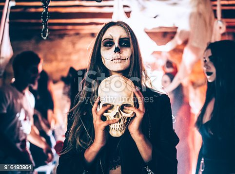 Young woman with santa-muerte make-up and disguise holding skull at Halloween dungeon party