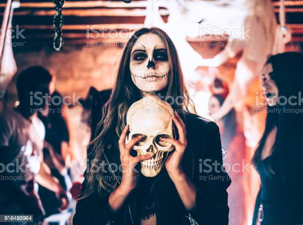 Young woman with skeleton makeup holding skull at halloween party picture id916493964?b=1&k=6&m=916493964&s=612x612&h=zyhtiv5kysxzscsnmumzdvgvk7loode42y8ztq26nds=