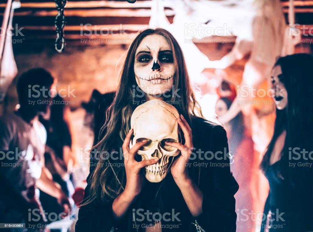 Mujer joven con el cráneo de esqueleto maquillaje celebración en fiesta de Halloween - foto de stock
