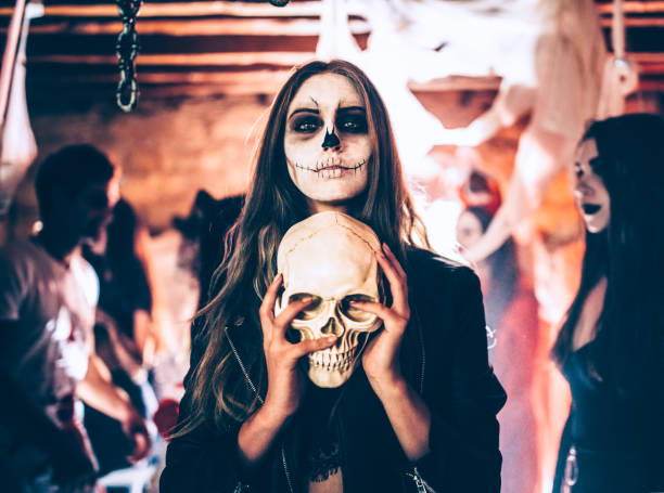 Young woman with skeleton make-up holding skull at Halloween party Young woman with santa-muerte make-up and disguise holding skull at Halloween dungeon party costume stock pictures, royalty-free photos & images