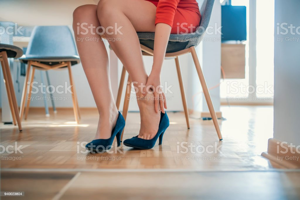 Young woman with slim legs feeling ache because of wearing high heels stock photo
