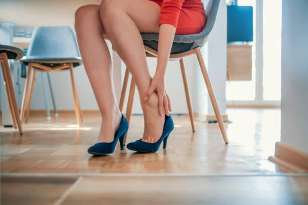 junge frau mit schlanken beinen fühlen schmerz wegen tragen von high heels - druck strumpfhosen stock-fotos und bilder