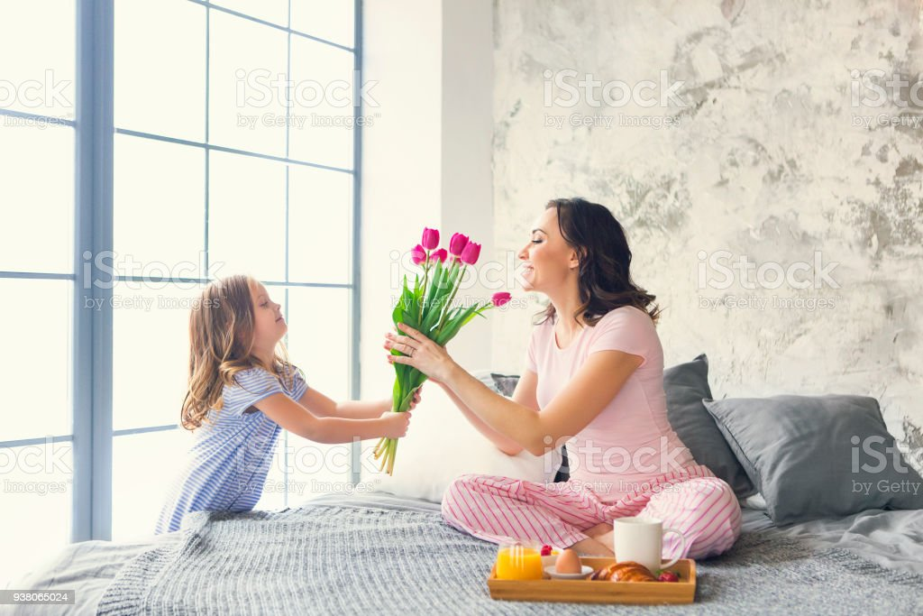 Young woman with small girl and flowers stock photo