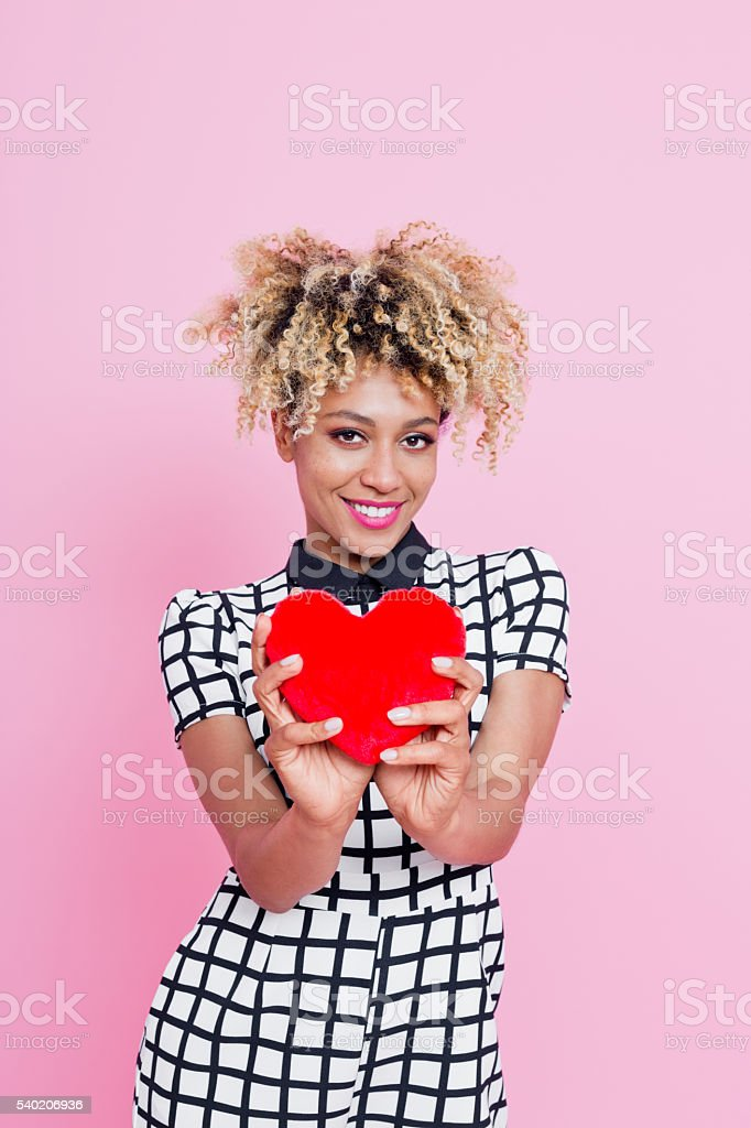 Young woman with small red heart Portrait of beautiful afro american young woman wearing grid check playsuit, standing against pink background and holding Red Heart. 20-24 Years Stock Photo