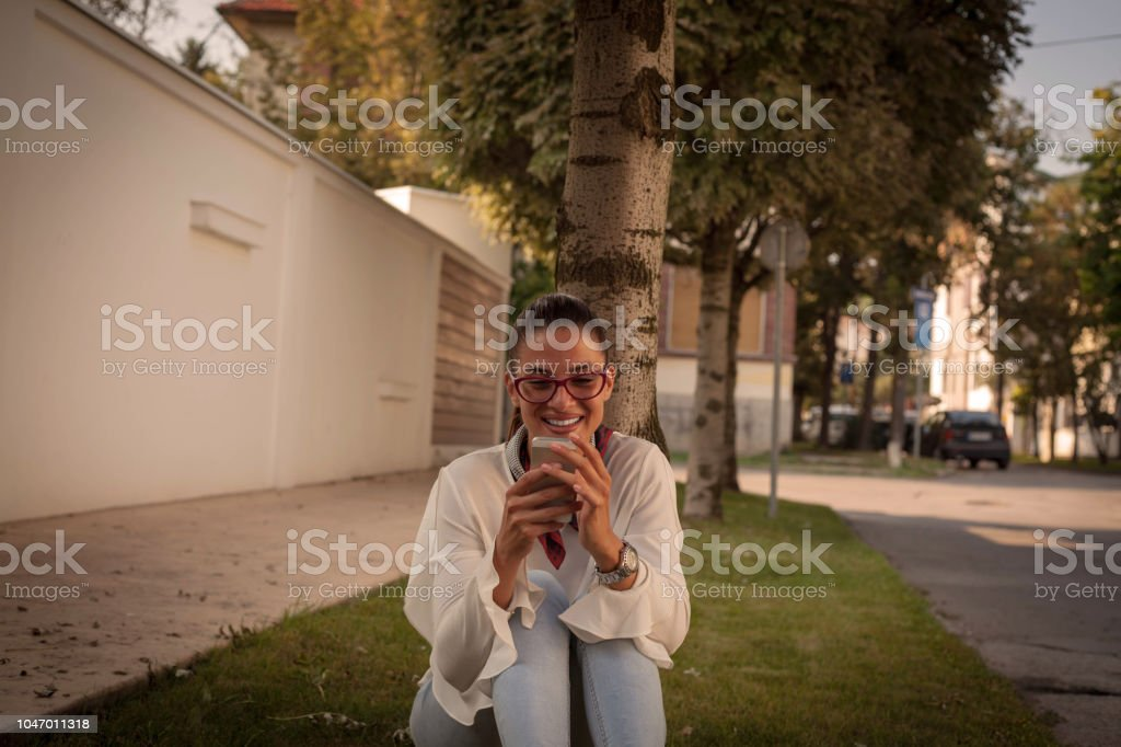 Smiling woman texting on phone.