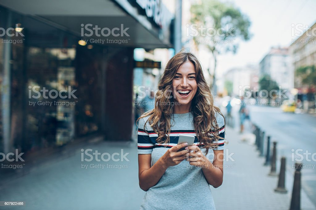 Young woman with smart phone laughing on the street stock photo
