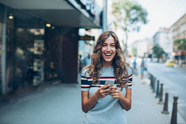 Young woman with smart phone laughing on the street - Photo