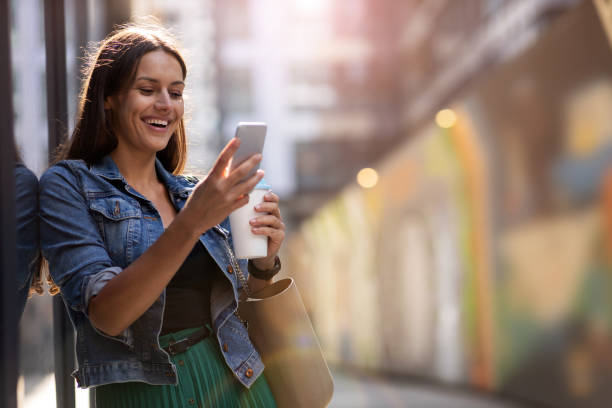 Young woman with smartphone and coffee in the city stock photo
