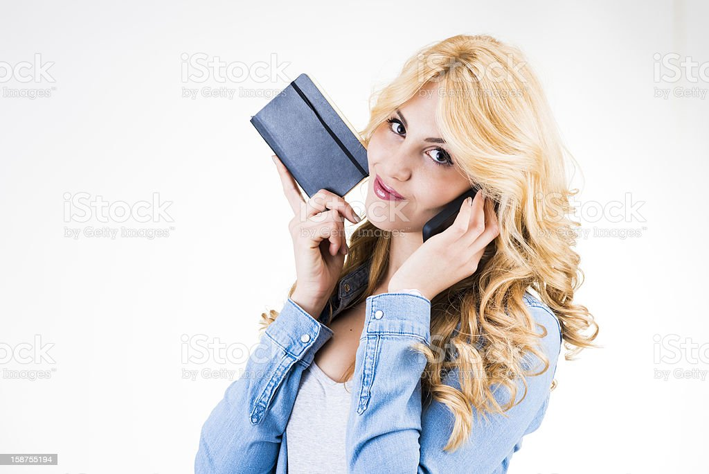 Young woman with smartphone and notepad royalty-free stock photo