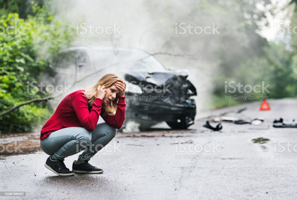 A young woman with smartphone by the damaged car after a car accident, making a phone call. stock photo