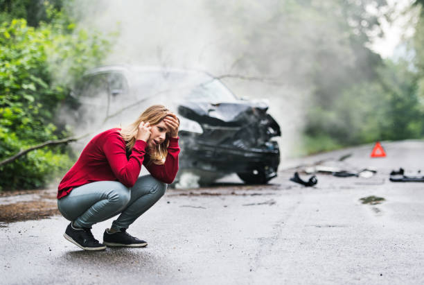 a young woman with smartphone by the damaged car after a car accident, making a phone call. - wrak zdjęcia i obrazy z banku zdjęć