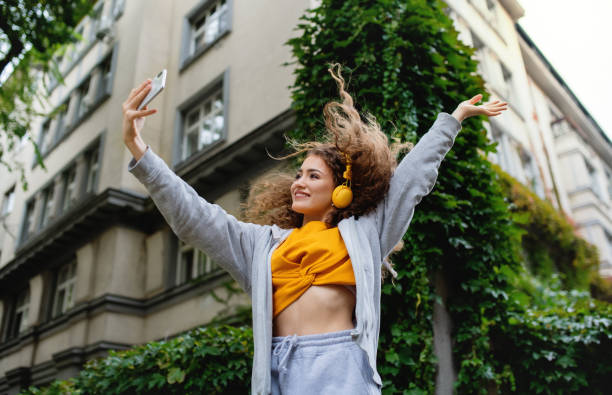 Young woman with smartphone dancing outdoors on street, tik tok concept. stock photo