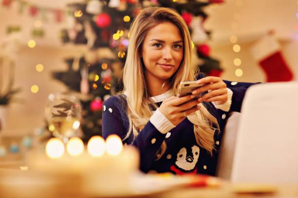 junge frau mit smartphone während der weihnachtszeit zu hause - weihnachtsprogramm stock-fotos und bilder