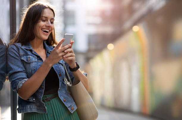 Young woman with smartphone in an urban city area stock photo