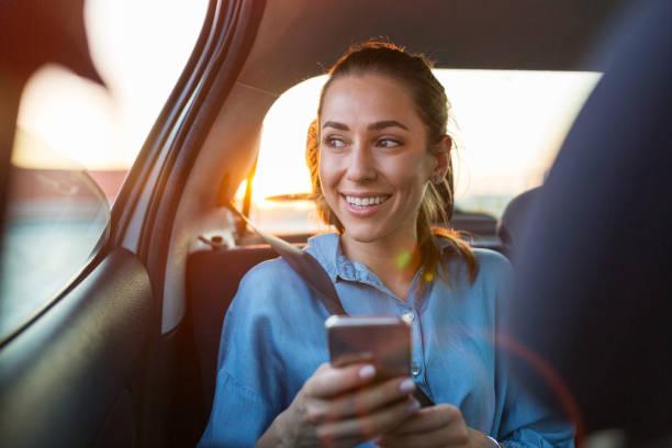 Junge Frau mit Smartphone auf dem Rücksitz eines Autos – Foto