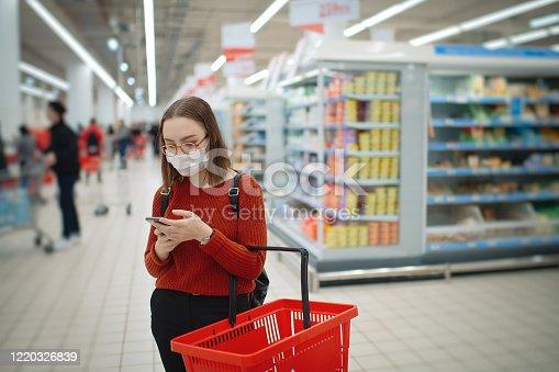 Female customer in a supermarket choosing goods