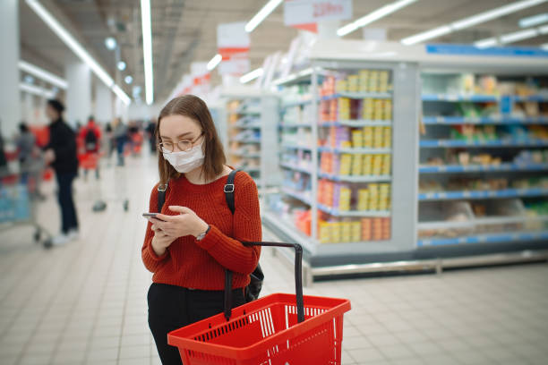 Young woman with smartphone shopping in a grocery store and wearing protective medical mask, social distancing and safe shopping concept