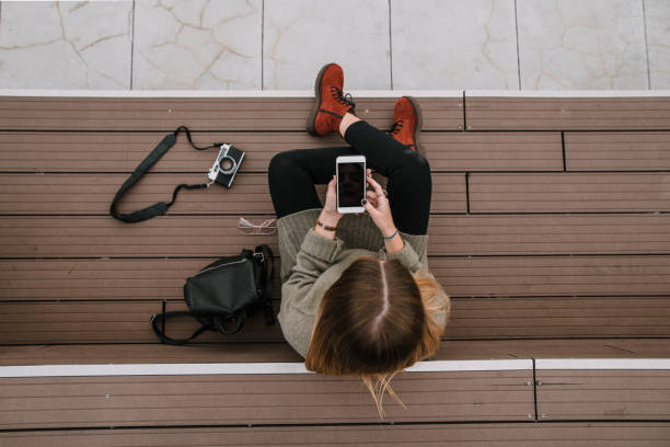 Young woman with smartphone sitting on staircase stock photo