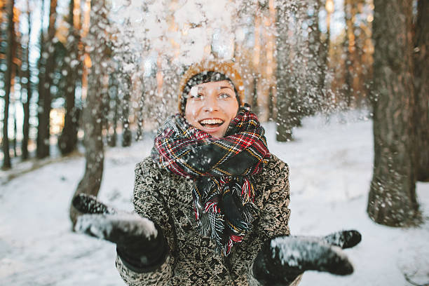 Young woman  with snow in hands in winter forest stock photo