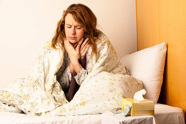 Young woman with sore throat in bed stock photo