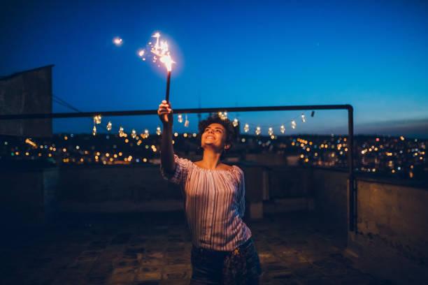 junge frau mit wunderkerze auf dach - terrassen lichterketten stock-fotos und bilder