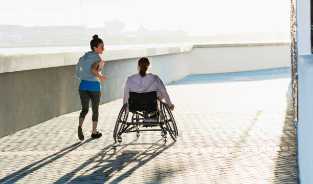 Young woman with spina bifida, Hispanic friend jogging stock photo