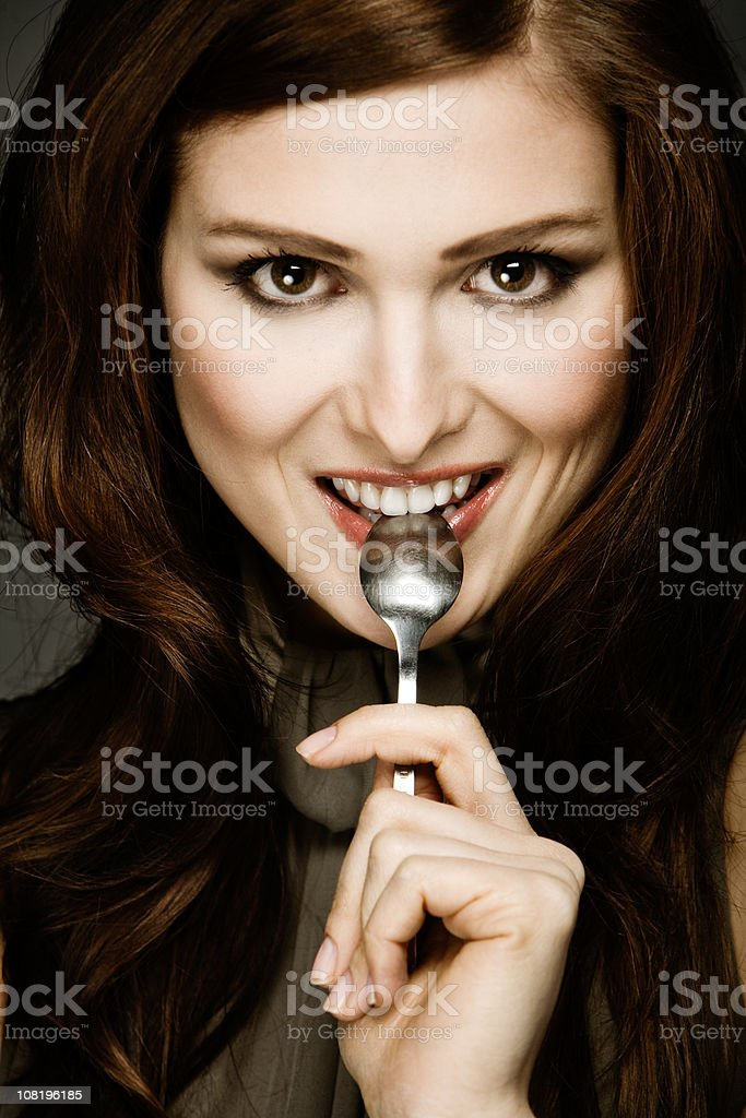 Young Woman With Spoon in Mouth royalty-free stock photo