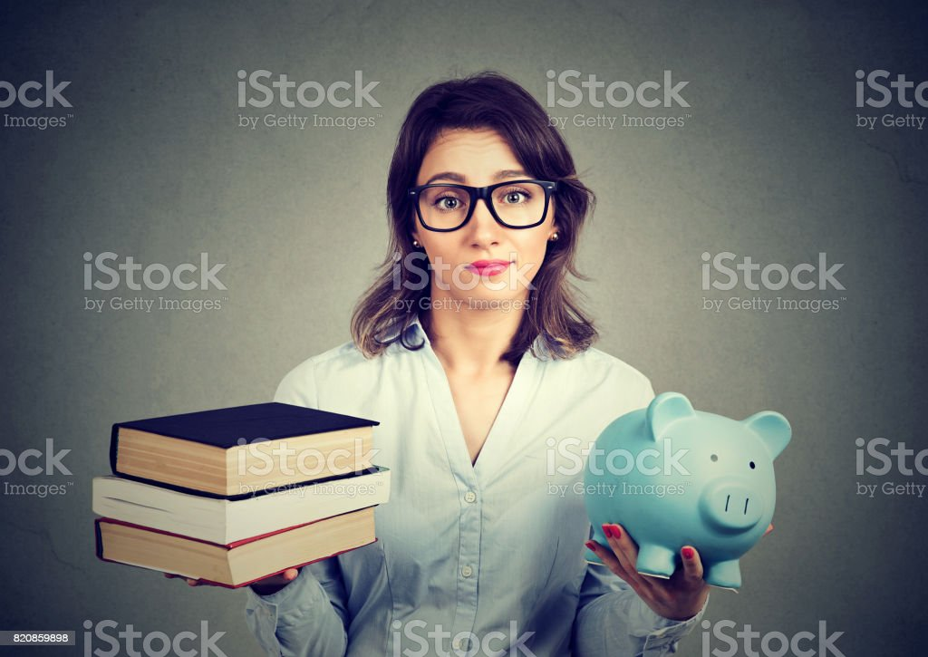 Young woman with stack pile of books and piggy bank full of debt rethinking future career path stock photo