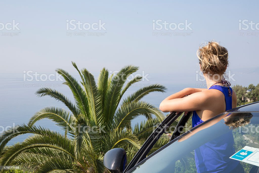 Young woman with steps out of car in Tropical environment stock photo