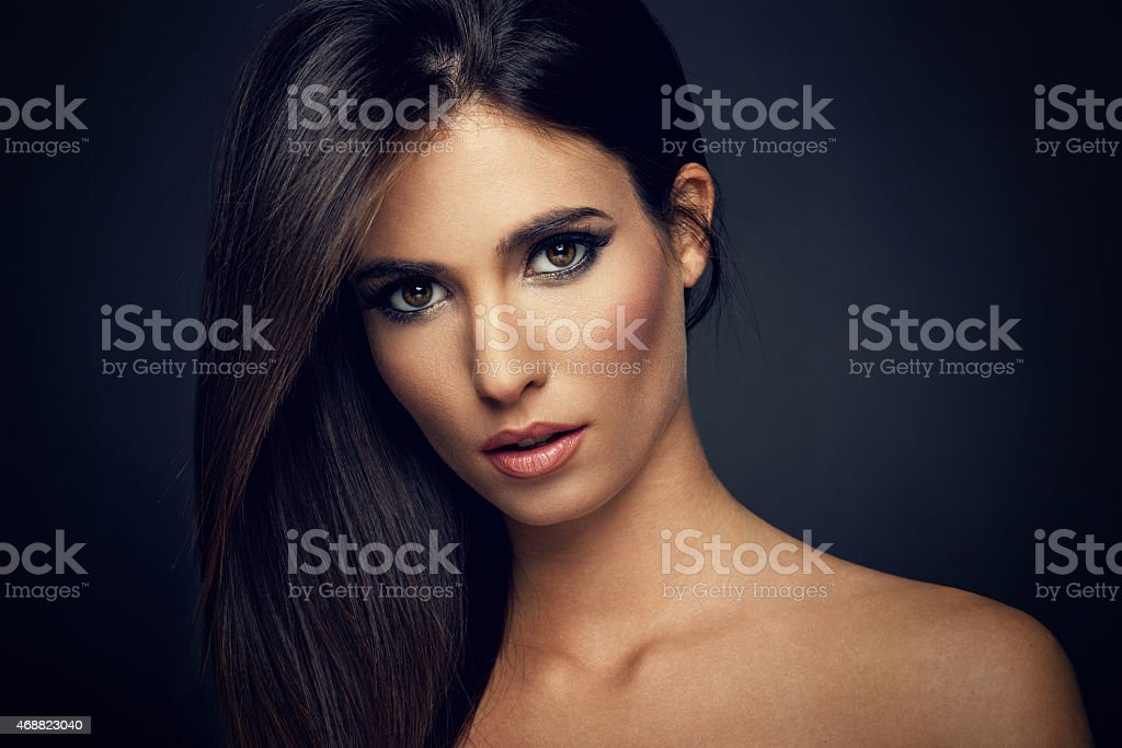 Young woman with straight hair on dark background stock photo