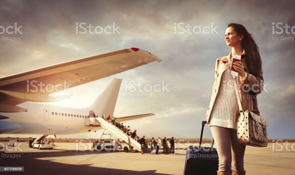 Young woman with suitcase arrived at the airport stock photo