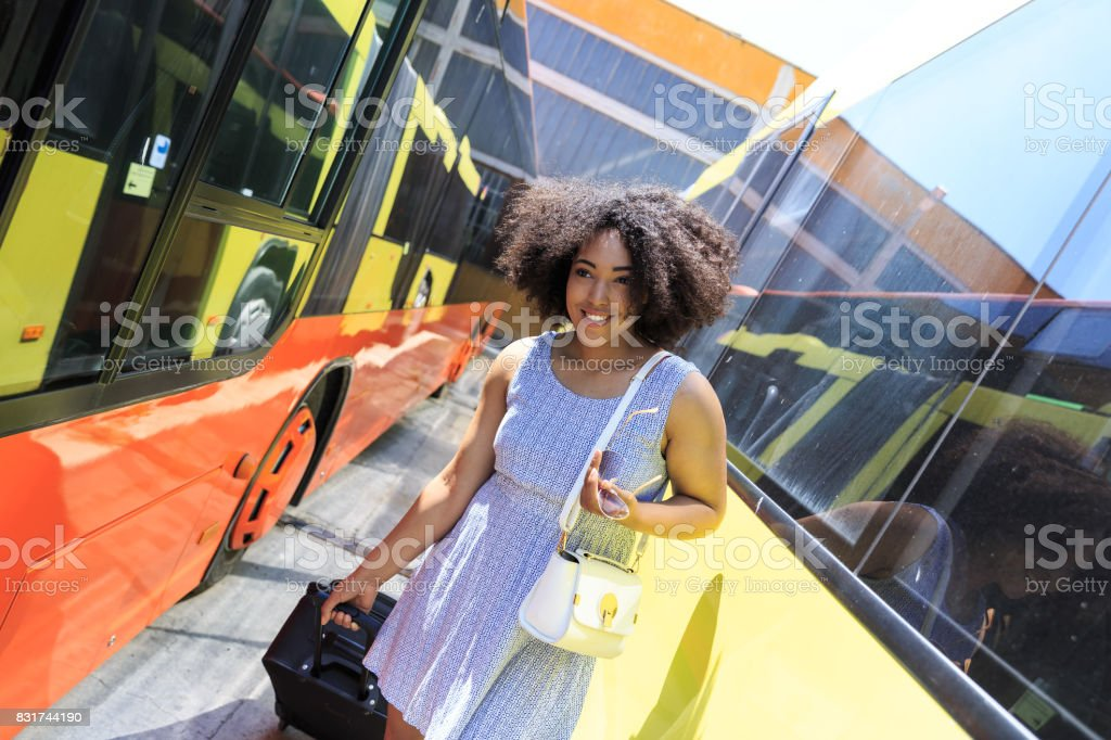 Young woman with suitcase going on bus stock photo