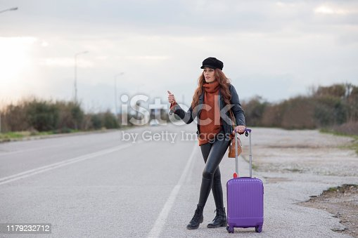 Young woman with suitcase hitchhiking