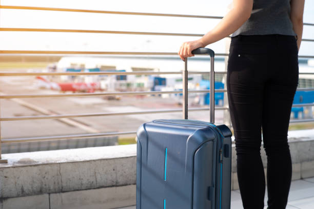Young woman with suitcase in airtport Young woman with suitcase in airtport carry on luggage stock pictures, royalty-free photos & images
