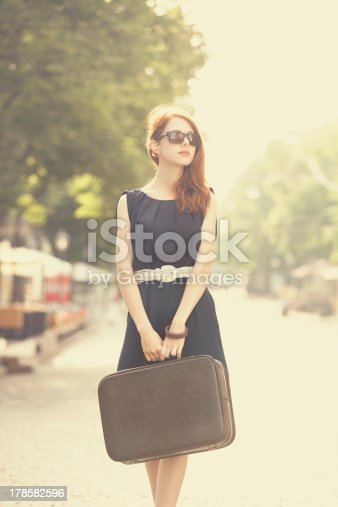 istock Young woman with suitcase on the city street 178582596