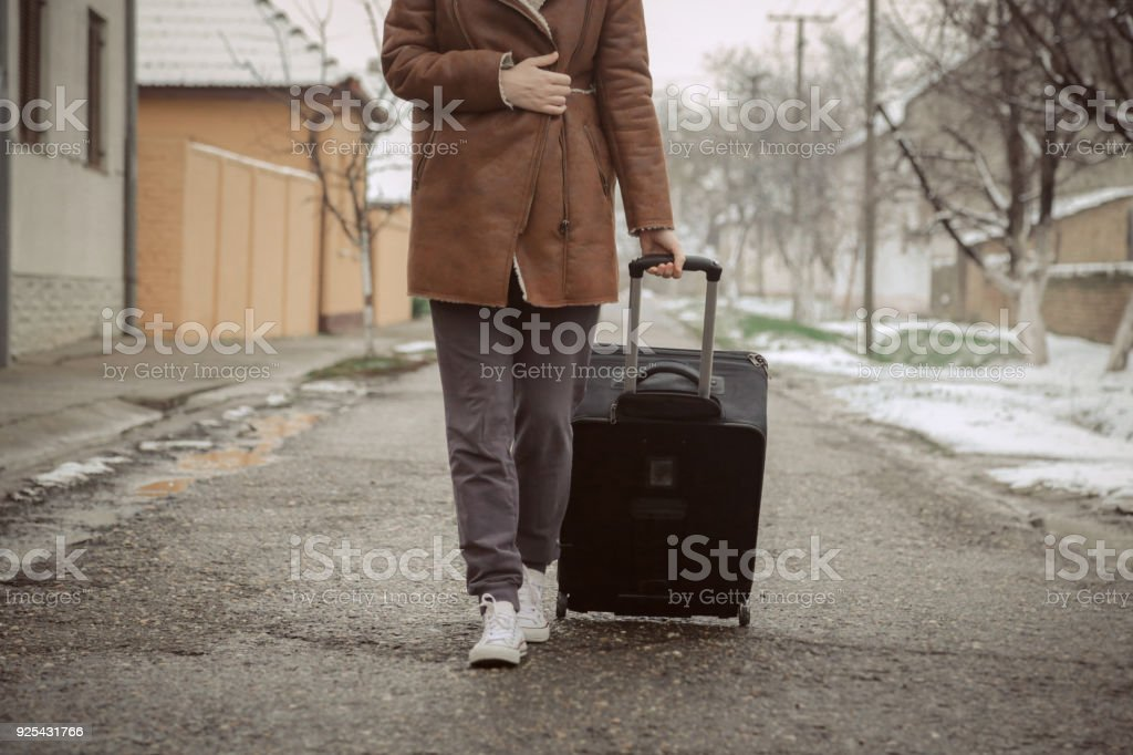 Young woman with suitcase on the street stock photo