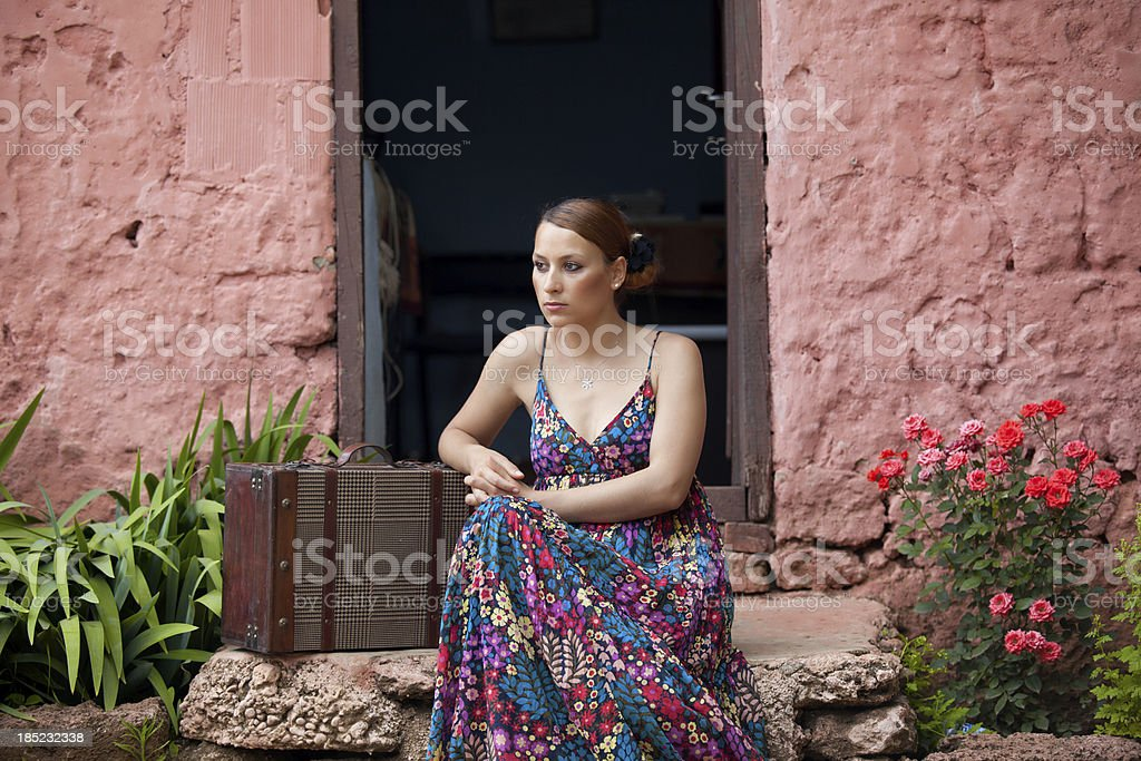 Young woman with suitcase ready to leave home stock photo