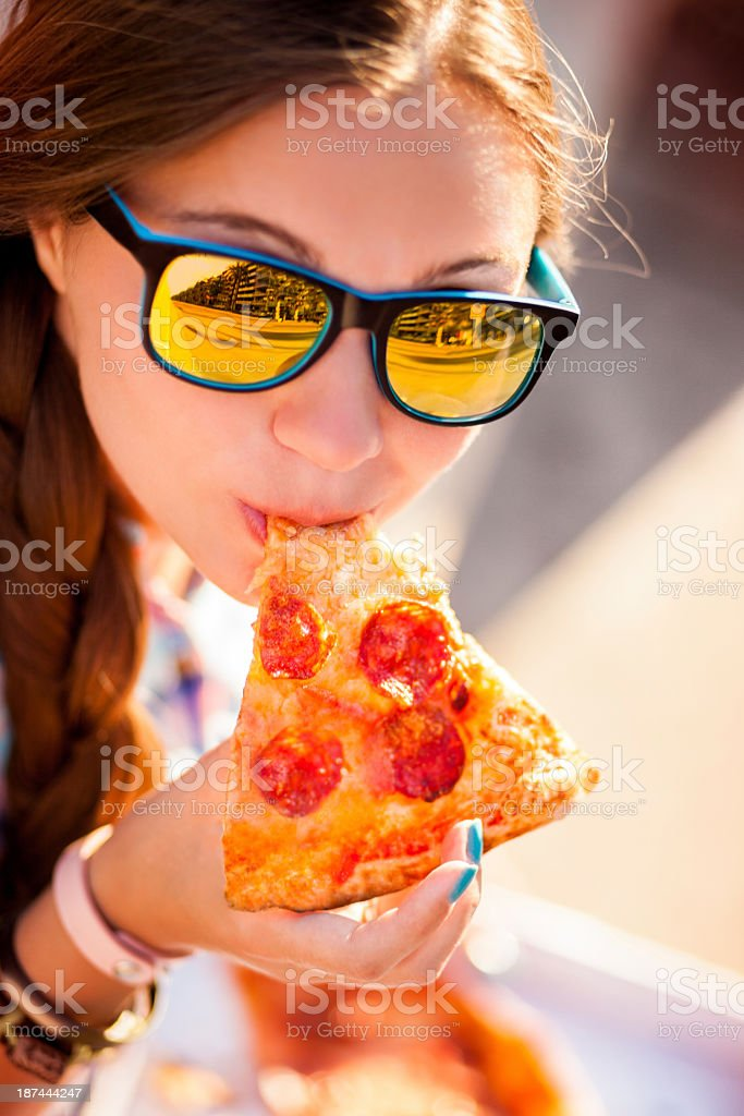 Young Woman With Sunglasses Eating Pizza royalty-free stock photo