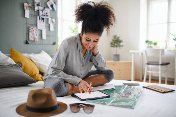 Young woman with tablet and map indoors at home, planning traveling trip. stock photo