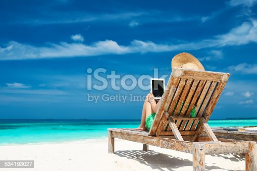 476618818 istock photo Young woman with tablet pc at the beach 534193027